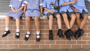 Children's legs and feet in black shoes hanging down